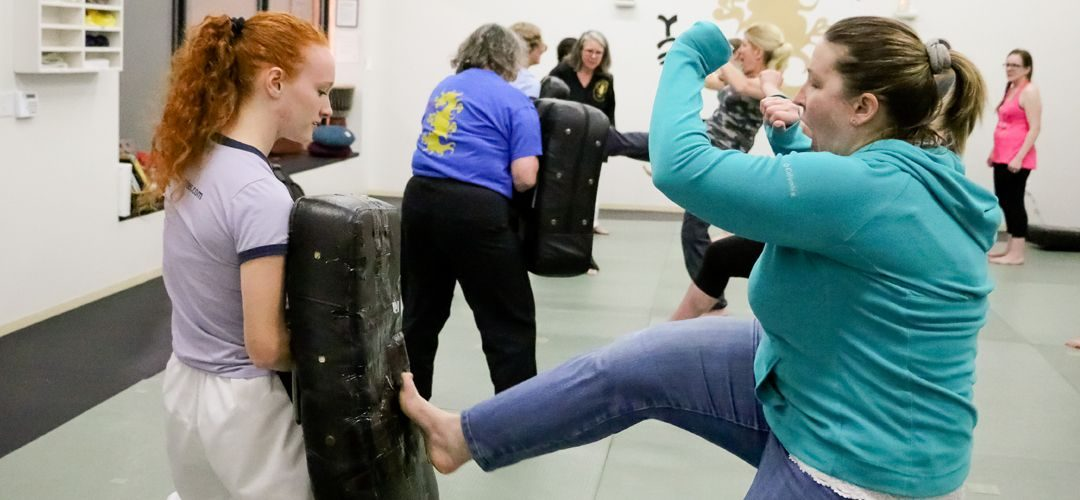 Female students in NAGA Martial Arts School's empowerment training classes located in Beaverton, OR. One of the students is training kicks while the other student is holding a kicking target.
