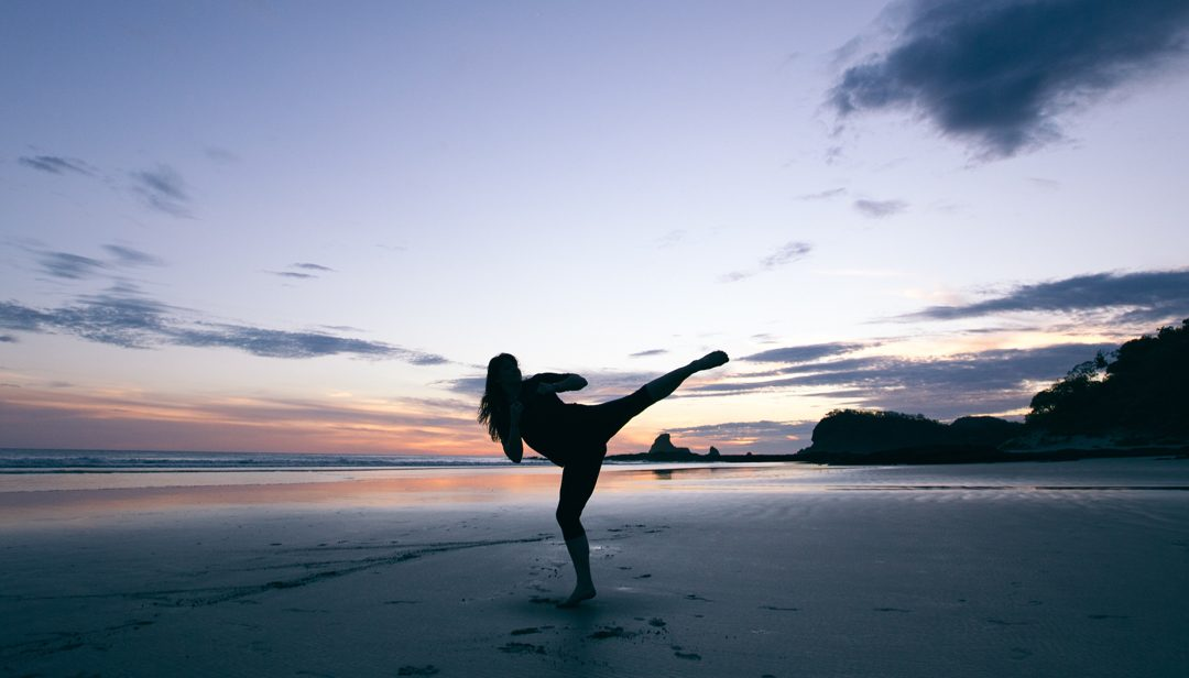 A woman doing an air kick on the beach during sunset.